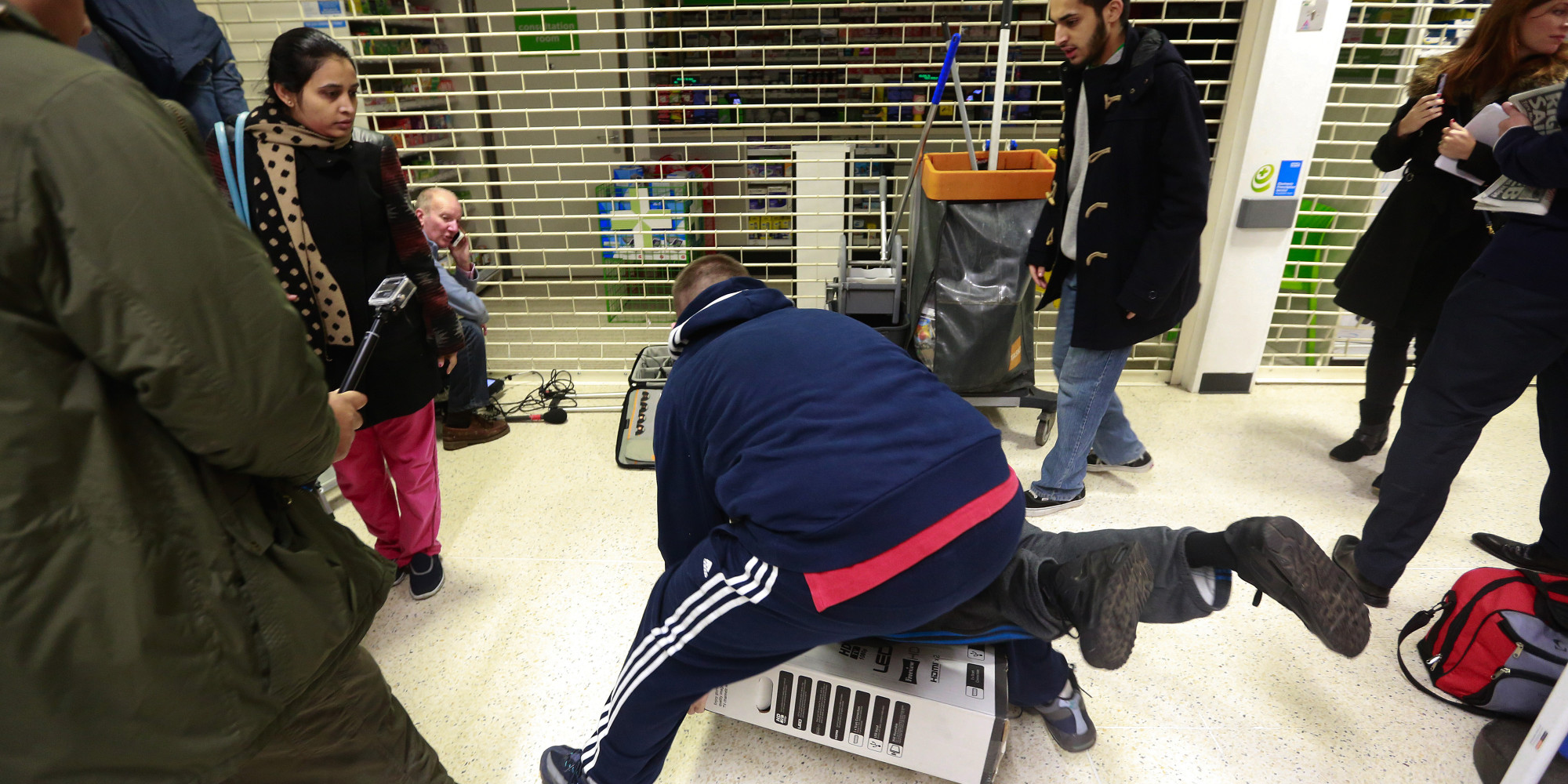 Customers fall to the floor as they grapple for an LED television during a Black Friday discount sale at an Asda supermarket, operated by Wal-Mart Stores Inc., in the Wembley district of London, U.K., on Friday, Nov. 28, 2014. Black Friday has caught on in the U.K. and worldwide over the last few years as the rise of the Internet has made the event a global phenomenon, with customers always being just one click away from the deals offered by U.S. retailers online. Photographer: Simon Dawson/Bloomberg via Getty Images